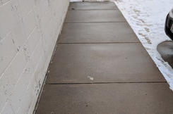 de-icing ice management as a post treatment on a sidewalk in Minneapolis after liquid salt brine application